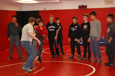 The wrestling coach shows a demonstration to the team with another wrestler. Credit: Casey Kim '20/SPECTRUM