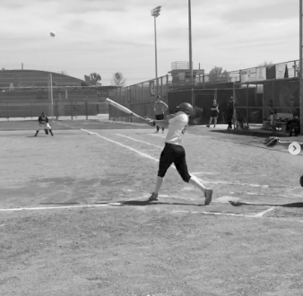 A softball player swings bat after making contact with the ball. Credit: Casey Kim'20/SPECTRUM